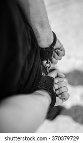 A man hands in handcuffs behind his back. Selective focus with shallow depth of field. Black and white toning.