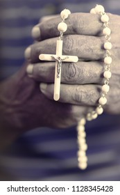 The man hands hold a rosary