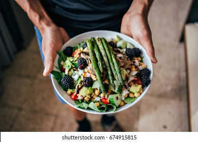 Man hands holding big deep plate full of healthy paleo vegetarian salad made from fresh organic biological ingredients, vegetables and fruits, berries and other nutritional things