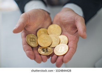 Man hands holding a lot of Bitcoin coins