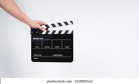 A man with hands is holding black Clapperboard or movie slate. it use in video production ,film, cinema industry.It is white background.
