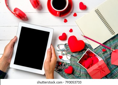 Man hands holding blank screen tablet on wooden white background with tablet,head phone and cup of coffee.Top view.