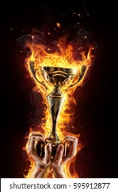 Man hands holding burning gold trophy cup as a winner, flames around. Concept of success and effort. Isolated on black background