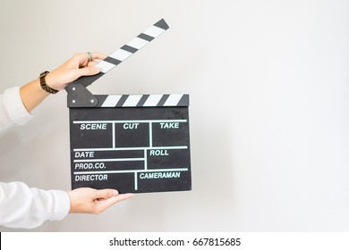 man hands holding clapper board for making video cinema in studio.Movie production clapper board or slate film concept.