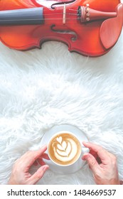 man hands holding coffee latte, enjoy playing violin in the morning. copy space on middle