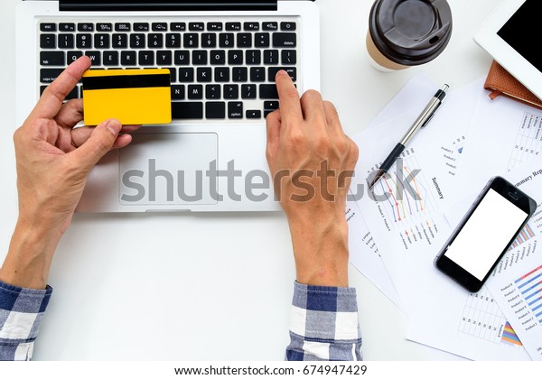 Man hands holding credit card and using laptop computer for buying online on desk table. Top view online shopping concept.