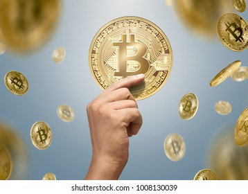 Man hands holding golden bitcoin with falling bitcoins on bright background