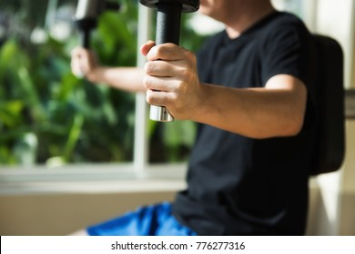 Man hands holding Gym machine in sport club with garden plant leaf background. Male athlete training chest muscles by pulling fitness equipment to work out strength alone.