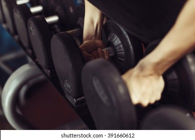 Man hands holding heavy gym weights.