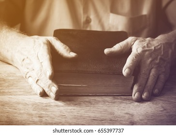 man hands holding   holy bible on wooden table, Vintage color