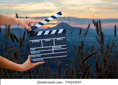 Man hands holding movie clapper isolated on nature background. Shown slate board. use the colors white and black.Realistic movie clapperboard. Clapper board isolated.Film director concept.