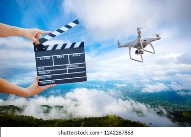 Man hands holding movie clapper.Film director concept. UAV drone copter flying for image catch motion in interview or broadcast wedding ceremony, catch feeling, hand hold Film Slate with drone copter.