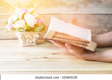 A man hands holding open old book with burred page on wooden background, Vintage color light effected