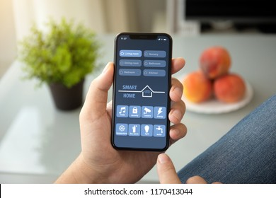 A man hands holding phone with app smart house in room home
