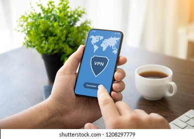 man hands holding phone with app vpn creation Internet protocols for protection private network on screen over table in office