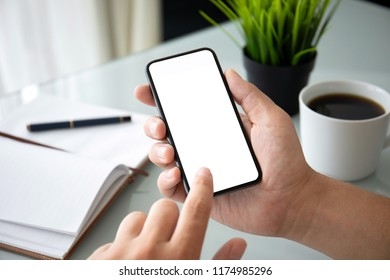 man hands holding phone with isolated screen over table in the office