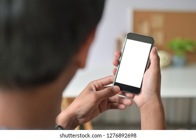 Man hands holding smart phone with blank copy space screen for your text message or information content, male reading text message on telephone during in office desk urban setting.