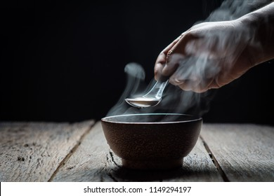 Man hands holding spoon with bowl of soup on a wooden in the dark. healthy food
