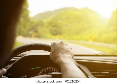 Man hands holding steering driving car on the road with mountain background and sunset