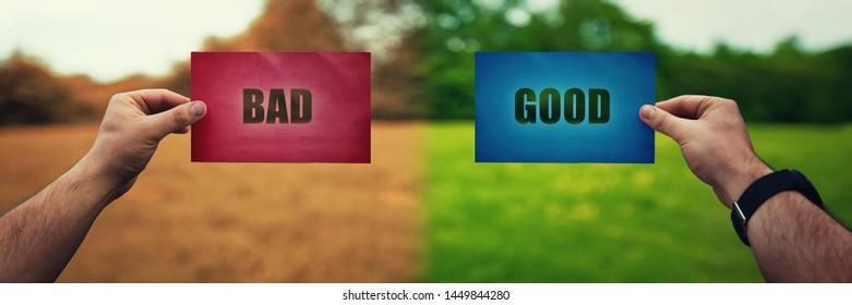 Man hands holding two colored paper sheets with opposite text good and bad over different nature environment background. Life dilemma, taking the right decision, correct choice.