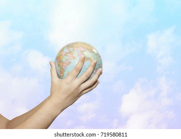 Man Hands holding World globe over cloudy pastel pink blue sky background, Earth Care Concept, conceptual image.