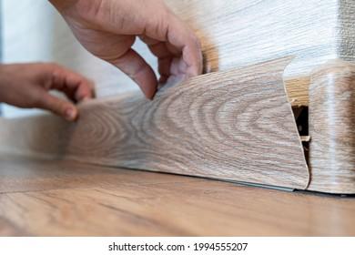 Man hands intall floor plastic skirting boards. replacement of the plastic skirting board on the floor. selective focus on the skirting board