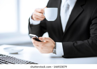 man hands with keyboard holding smartphone and drinking coffee