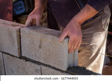 Man Hands Laying Concrete Building Block in The Wall in Progress