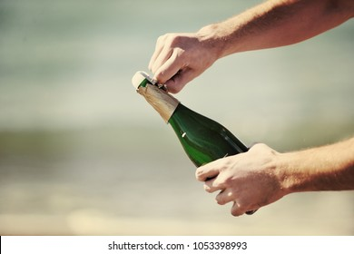 man hands open bottle of champagne alcohol and wine drink outdoor on party celebration event