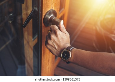 Man hands open the wood door.
