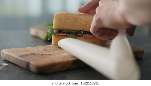 man hands packing ciabatta sandwich with salami and cheese