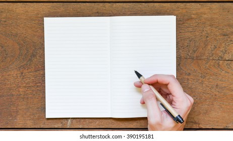 Man hands with pen writing on empty notepad over wooden table.