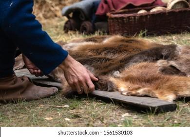 Man hands picking up wild animal fur of the ground. Animal coat skin for sale at rural village