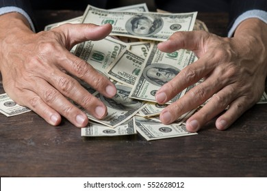 Man hands in pinstripe suit sweeping pile of us banknotes on old wooden table,business concept.Pile of money.
