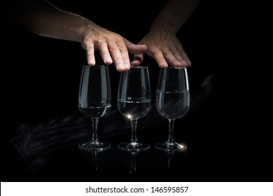 Man hands play music on glass cups filled with water. On the black bakground