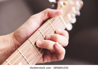 Man hands playing acoustic guitar, close up chord guitar player - selective focus