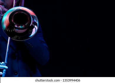 a man hands playing on a trombone black background