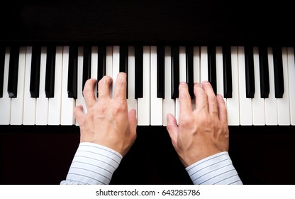 Man hands playing piano. Classical music. Art and abstract background. Asian man pianist. Top view. Dark vignette.
