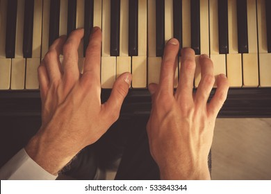 Man hands playing piano, close up
