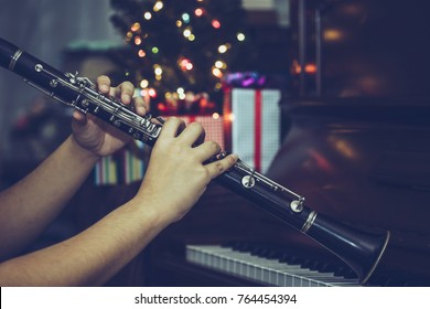 A Man hands plays Clarinet over piano  with Christmas tree and gift boxes in the night