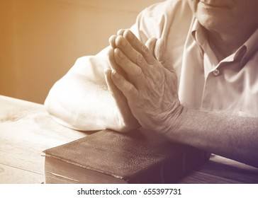man hands praying on holy bible on wooden table, Vintage color
