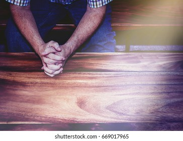 man hands praying on wooden table with window light effected, christian background