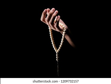 Man hands praying with prayer beads over dark background. Muslim Pray