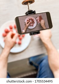 Man hands preparing meatballs with raw mincemeat recording video on smartphone. Lifestyle close up composition with natural light. Homemade cooking vlogger influencer streaming blogging concept