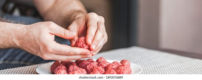Man hands preparing meatballs with raw mincemeat. Lifestyle close up composition with natural light. Homemade cooking during lockdown, stay home housekeeping sharing concept. Side view with copy space