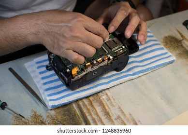 Man Hands Repair Broken Film Camera, Photograph Workplace.Freelance concept work at home.
