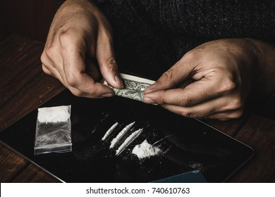 Man hands rolls dollar banknote for using cocaine powder lines, Drug addiction concept