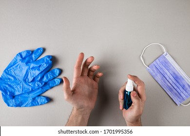 Man hands sanitizing on plain gray background. Hands disinfection during coronavirus minimal concept. syrgical mask on table.
