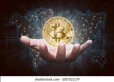 Man hands showing golden bitcoin as virtual money on digital world map background