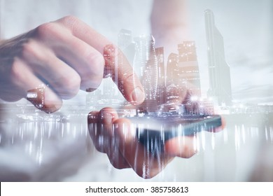 man hands touching smartphone, closeup, double exposure with modern city skyline